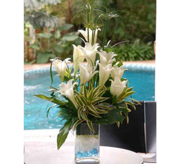 white lilies in clear glass