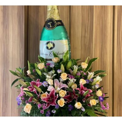 light pink and dark red lilies, champagne roses , purple eustoma and purple carnation spraywith a big champagne bottle balloon
